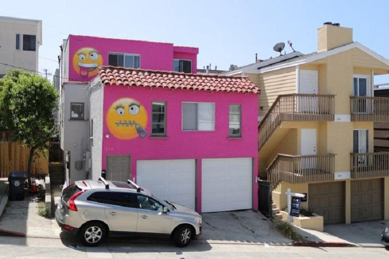 Bright pink house decorated with emojis is result of neighbor's quarrel