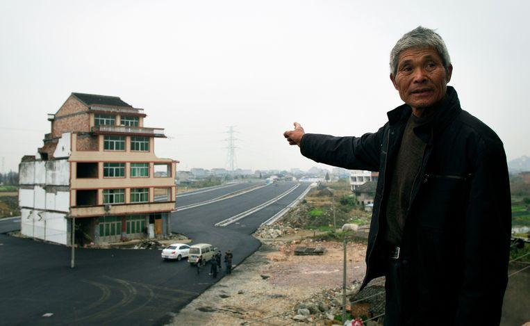 a main road has been built around a house in China.