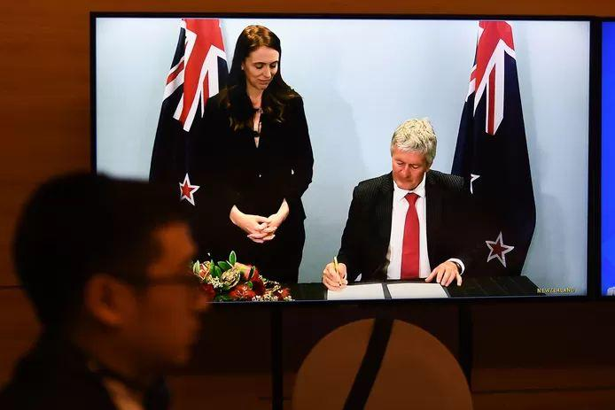 New Zealand Prime Minister Jacinda Ardern sees her trade minister, Damien O'Connor, sign his signature.
