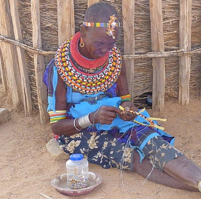 African woman weaves bead souvenirs